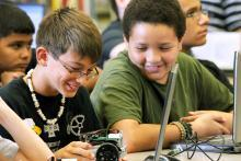 View: Students smiling and enjoying themselves as they work with a small hardware device