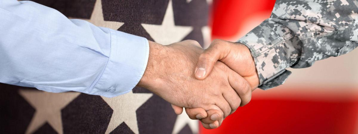 The hands of a civilian and a military member shake in front of a backdrop of the American flag.