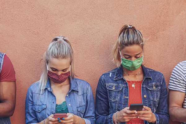 Four people wearing masks are looking at their smartphones.