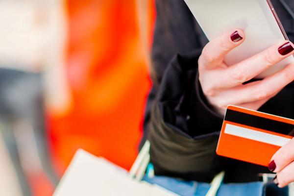 Woman holding her phone, shopping bags, and a credit card