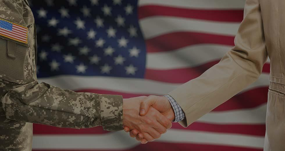 Two individuals, military and civilian, shaking hands. Links to Veterans: Launch a New Cybersecurity Career
