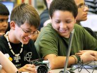 Two smiling students enjoying working on their small, car like, hardware device